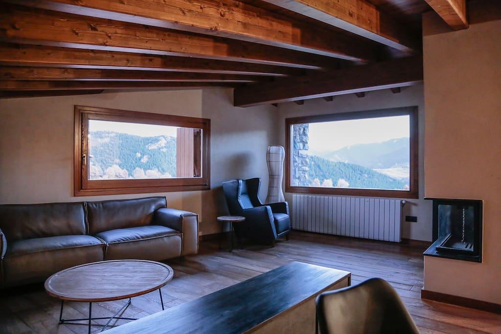 Comedor-salón amueblado con sofás y sillones de piel.  Chimenea.   Vistas al Cadí.