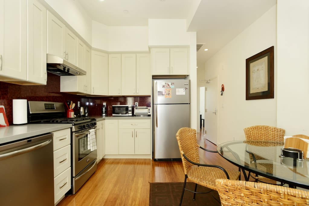 Huge full kitchen with brand new appliances, bamboo hardwood floors, and glass round table with wicker chairs