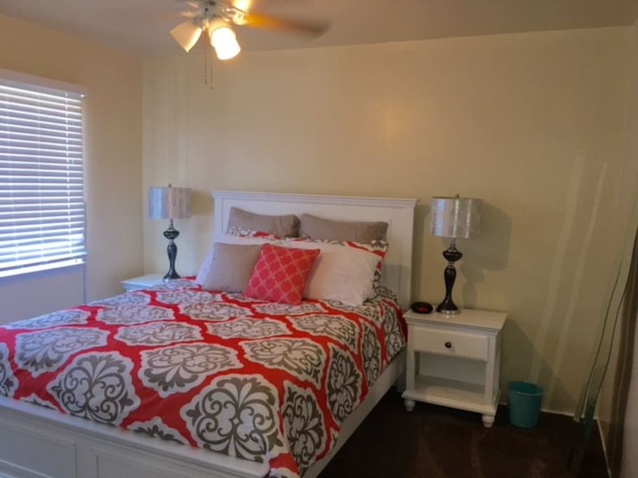 Lovely queen size bed with plenty of extra pillows, lamps, ceiling fan, and bedside clock.
