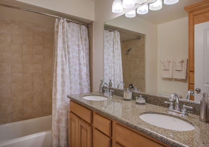 Master bathroom has a double vanity and a shower/tub combo with tile and granite.