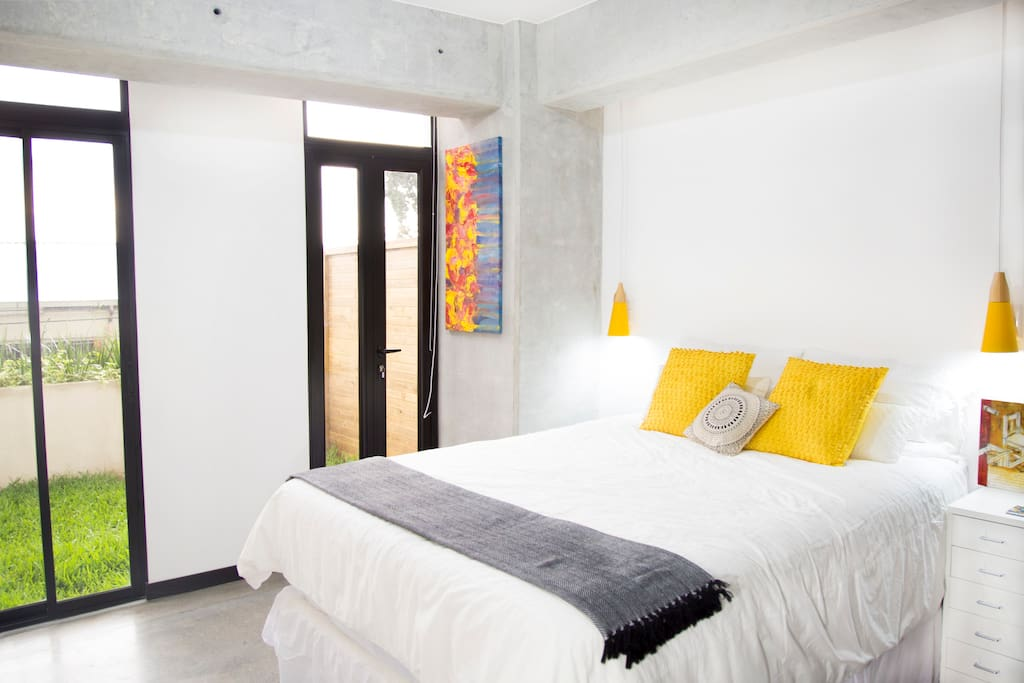 Master Bedroom / Queen size bed, smart TV, and access to garden