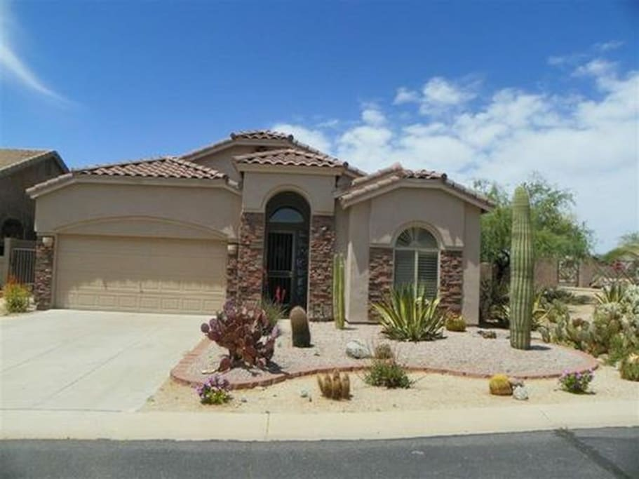 Desert landscaped gated residence includes guest driveway parking.