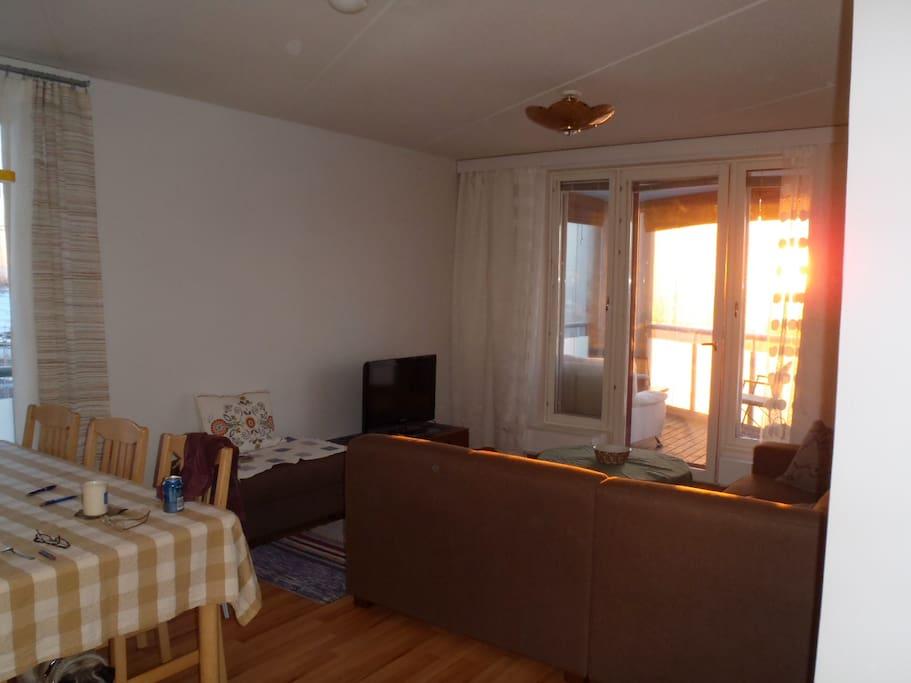 Olohuone jossa iso ja mukava kulmasohva ja käynti parvekkeelle