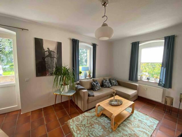 Wohnzimmer mit Ausgang zur Terasse und Schlafcouch
