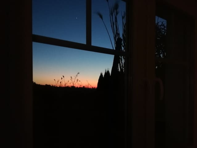 Fensterausblick im Herbst mit Abendrot