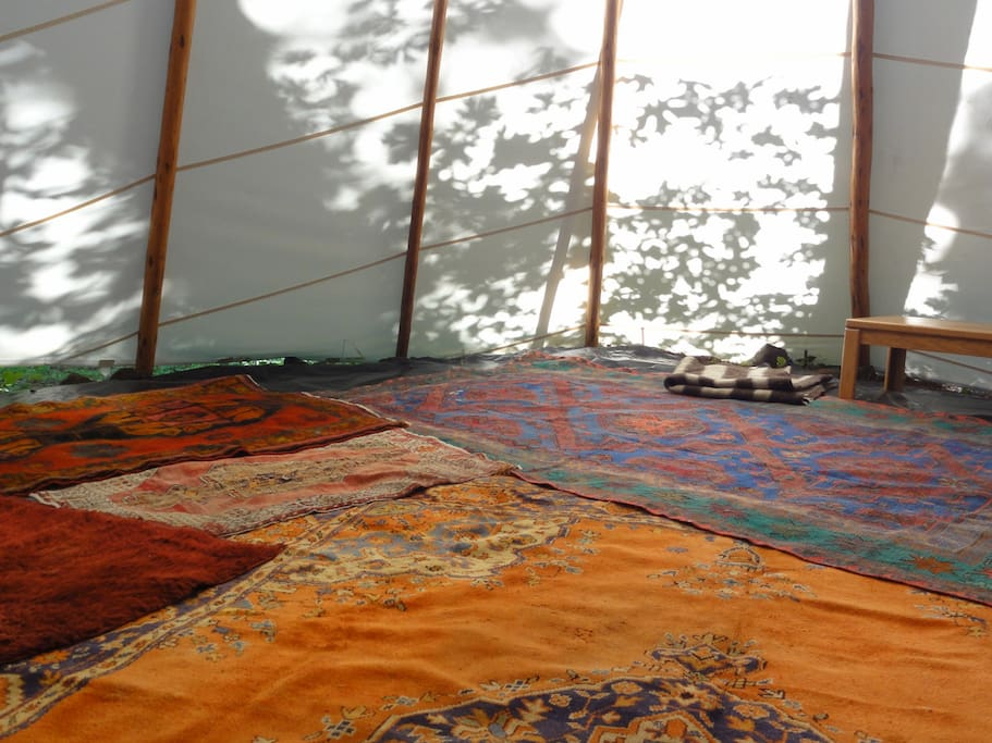 The rugs give this tipi a 'nomadic' feel. The floor is soft with wood chips and a moisture barrier.