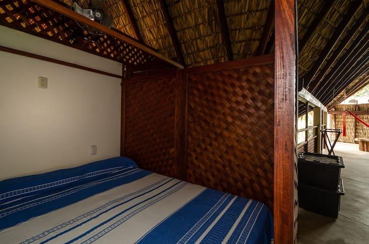 Cama matrimonial con ventilador y mosquitero. En un espacio privado dentro del mismo loft.
