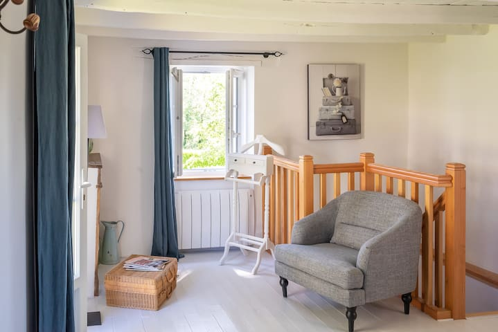 Coin détente dans l'espace nuit : fauteuil, magazine, chevalet et décoration raffinée. La chambre est dotée d'une porte-fenêtre donnant sur le parc et de deux fenêtres.