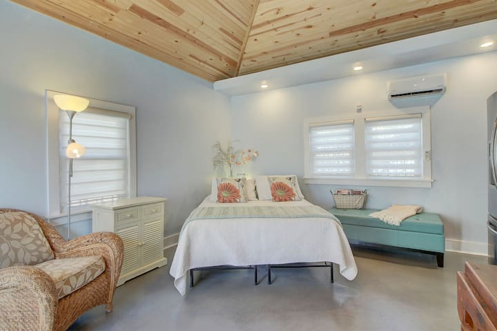 Bed area with nightstand; comfortable upholstered chair and ottoman for seating.