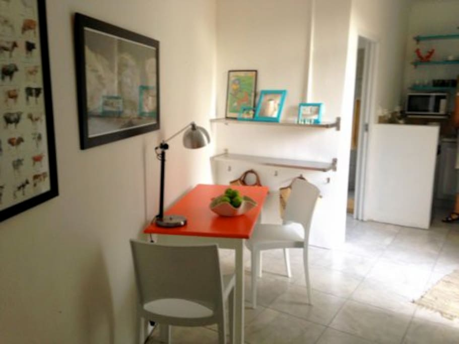 The table with chairs and kitchenette in background
