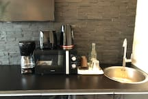Small kitchen with micro, coffeemaker, watercooker, toaster, fridge. Plates, cups and complimentary coffee and Tea included. No stove provided.