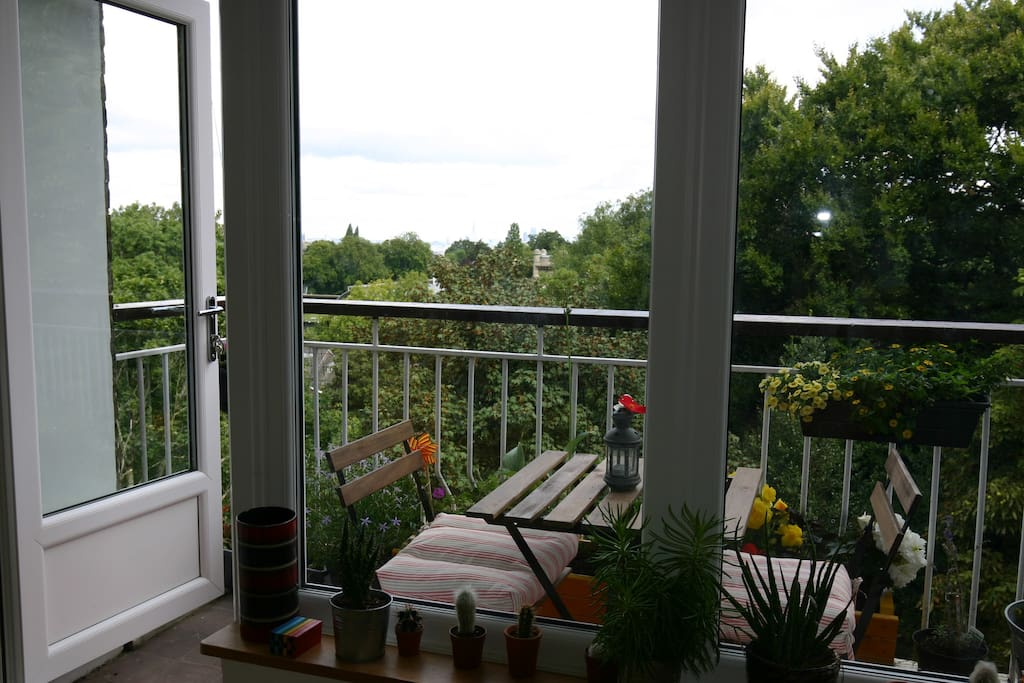 The balcony is surrounded by trees, and very private. You may even see a parakeet!