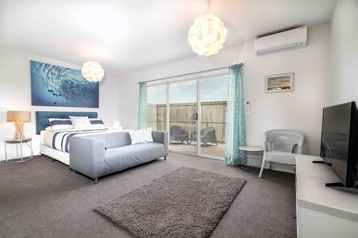The master suite is generously sized, with a couch, arm chair and Smart TV along with an ensuite and private balcony.