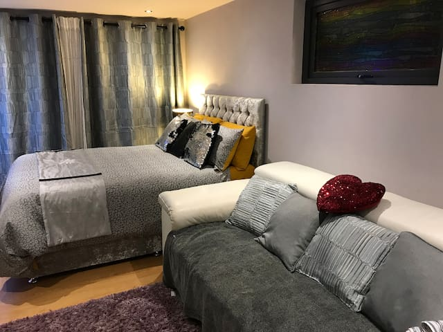 Main bedroom which also has a sofa and wide screen TV with Netflix, Disney and Prime available.  Double doors to the Private patio area