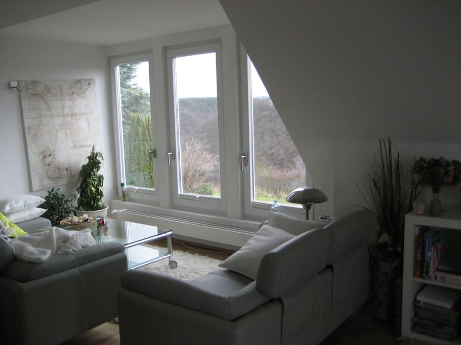Your Living room with lounge area and panorama window / Wohnzimmer mit grossem Sofa and Panorama-Fenster