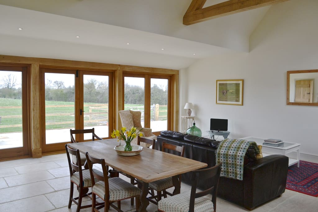 LIGHT & SPACIOUS LIVING/DINING AREA, OAK BEAMS & LIME STONE FLOOR. OAK FRENCH WINDOWS LEADING TO PAVED TERRACE AREA WITH RURAL VIEWS.