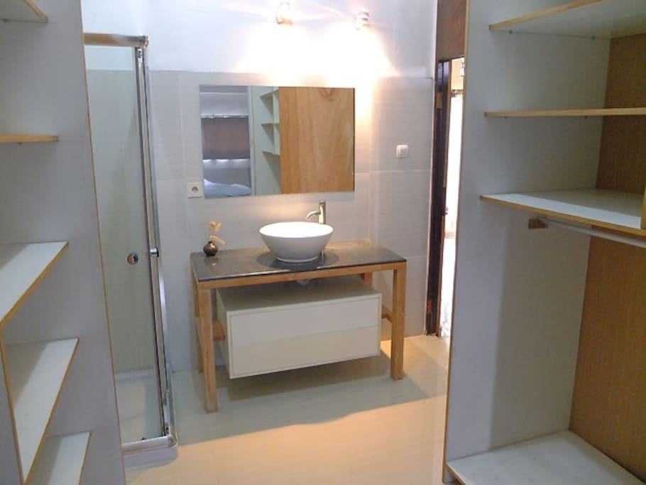 Here you can see part of wardrobe and shelves, also washbasin and mirror.
