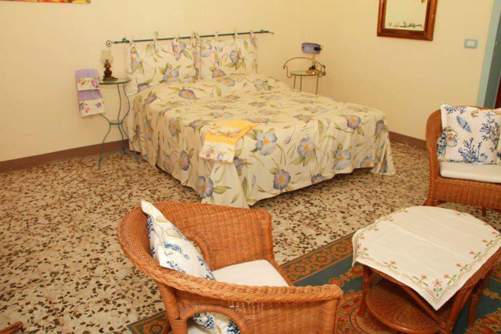 Camera matrimoniale con divanetto con lenzuola e asciugamani