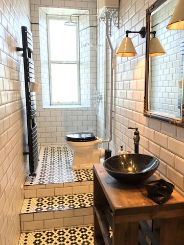 Our newly redone bathroom with a waterfall shower, high ceilings, huge heated towel rail, a classic pull-chain toilet, and lovely underfloor heating.