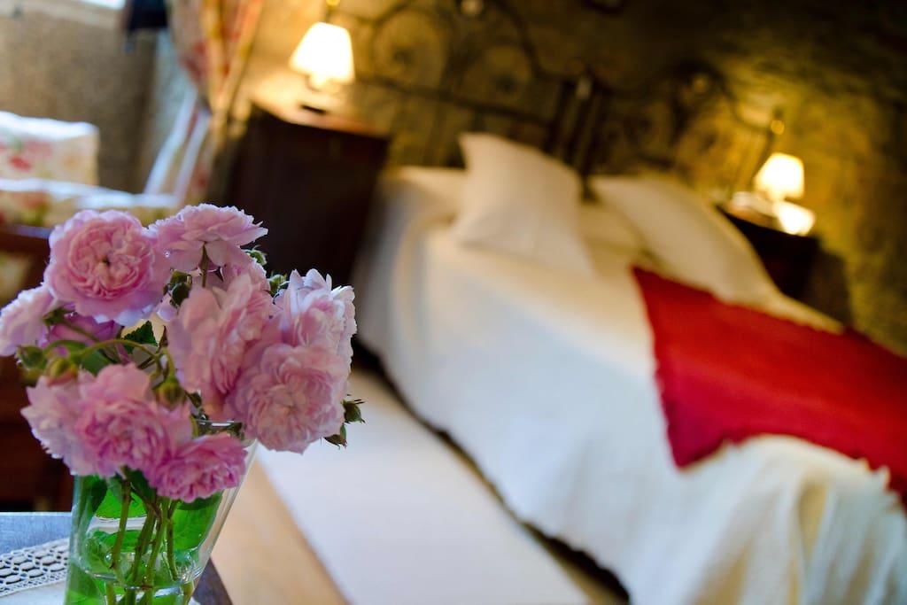 Confortable habitación doble de estilo rústico con vigas de madera y pared de piedra