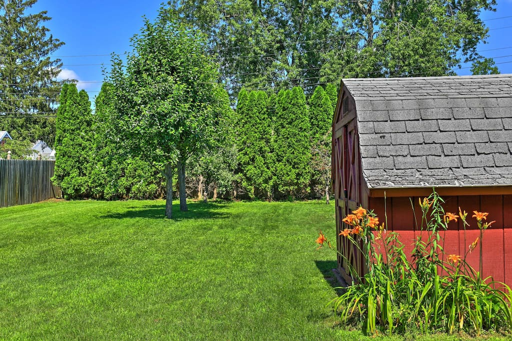 You'll enjoy spending time in the well-manicured backyard, which features a red shed.