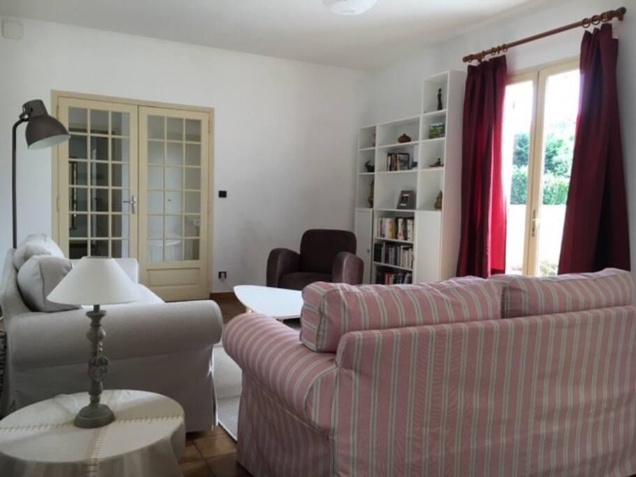 Le salon : deux canapés, un fauteuil, une bibliothèque.