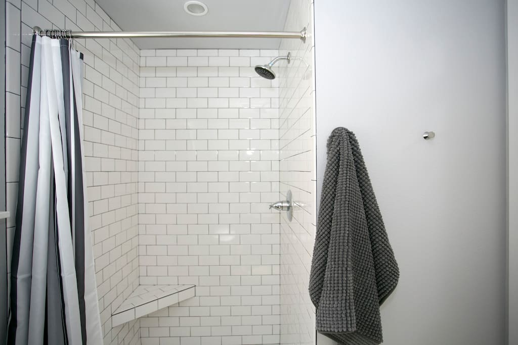 The roomy tile shower has great water pressure and a helpful little bench.