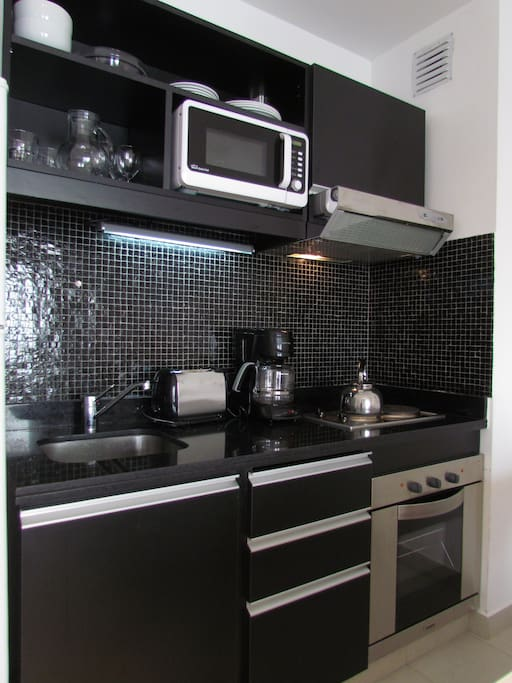 Fully equipped kitchen with new appliances and kitchenware and utensils