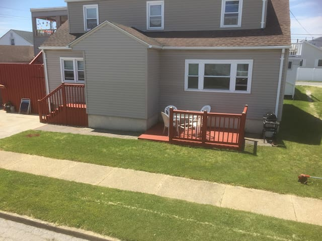 Front of house showing front entrance and outside deck with patio furniture and gas bbq