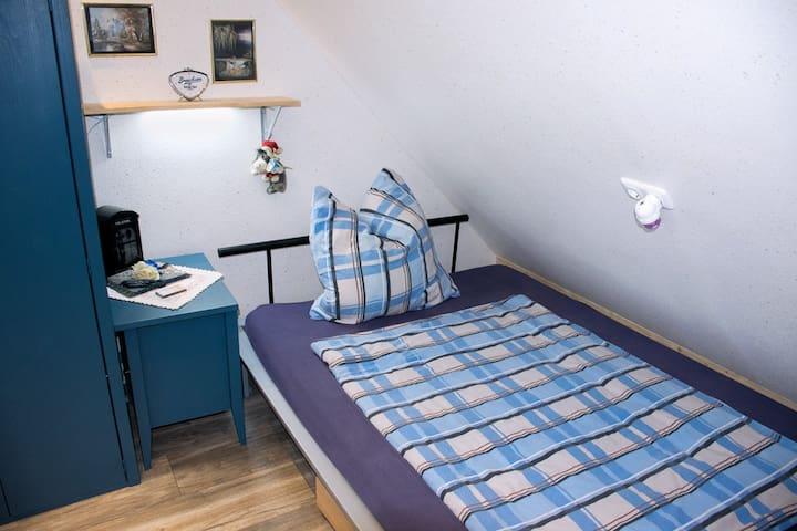 Gemütliches Einzelbett im blauen Zimmer.