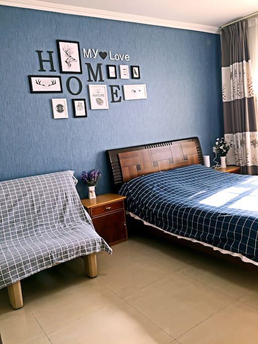 卧室的背景墙、双人床、单人沙发。