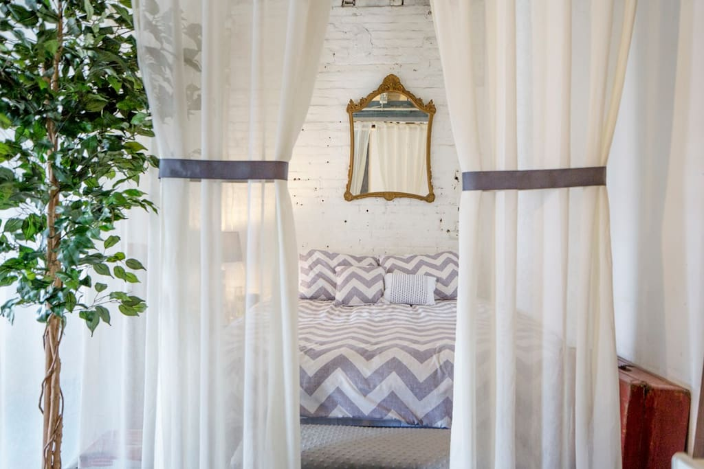 The queen sized bed with feather mattress topping and whimsical sheers hanging via invisible cords to create a sleeping oasis.