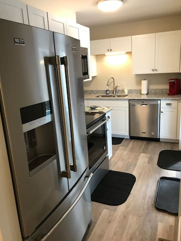 Brand new Maytag appliances in steel gray in the dishwasher, microwave, stove, and huge fridge in our L-shaped kitchen!