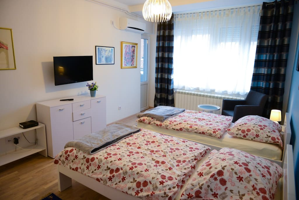 A cozy bedroom with 2 single beds, cable TV, balcony and AC