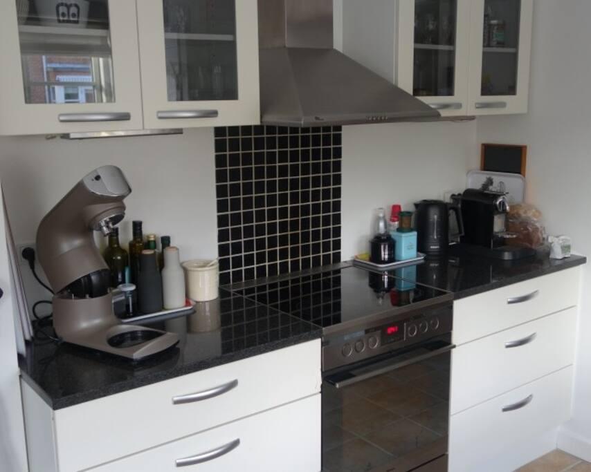 Køkken med køkkenmaskine og komfur m.m.