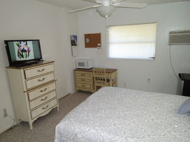Pleasant room with AC and LCD television. coffee pot and compact refrigerator in room