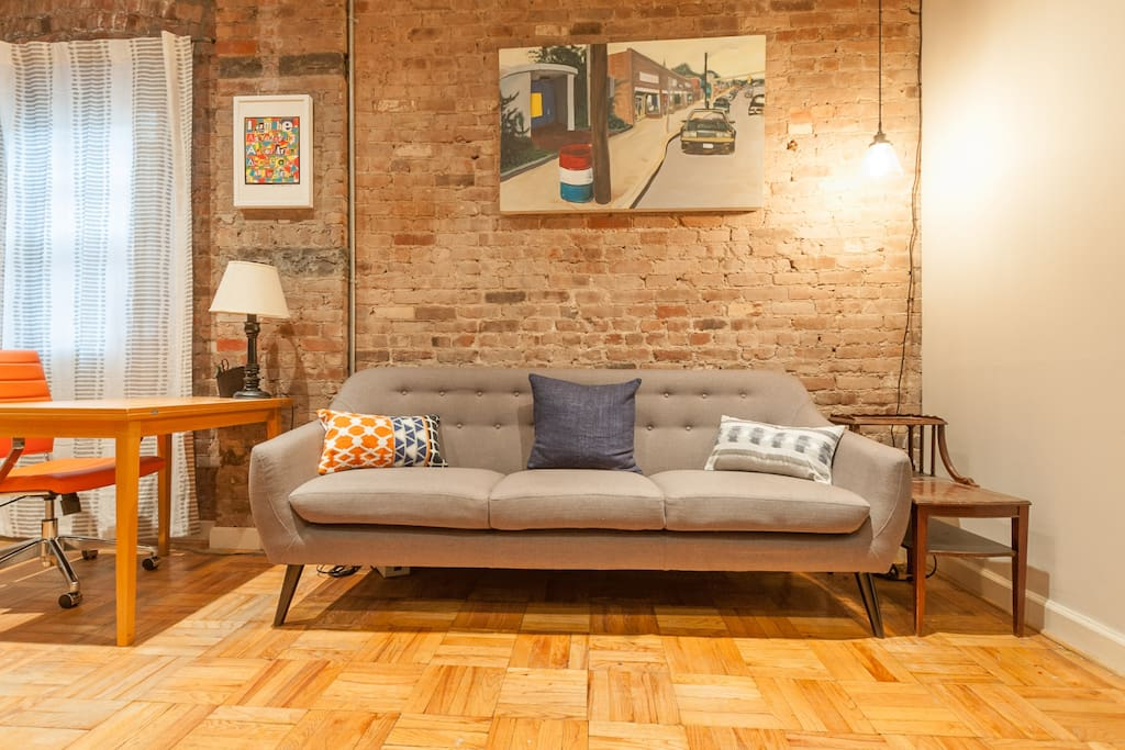 """New midcentury modern couch and """"Edison bulb"""" reading lamp."""