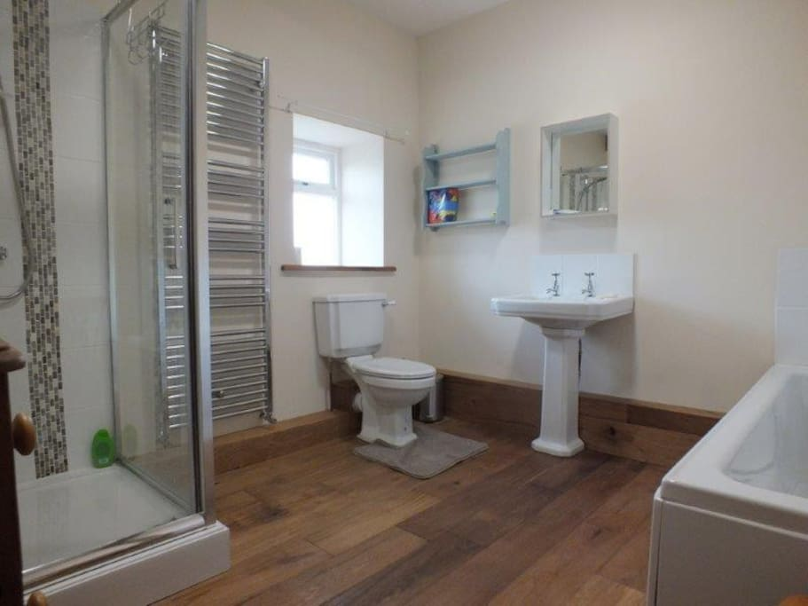 The upstairs bathroom is spacious with a huge shower and large bath