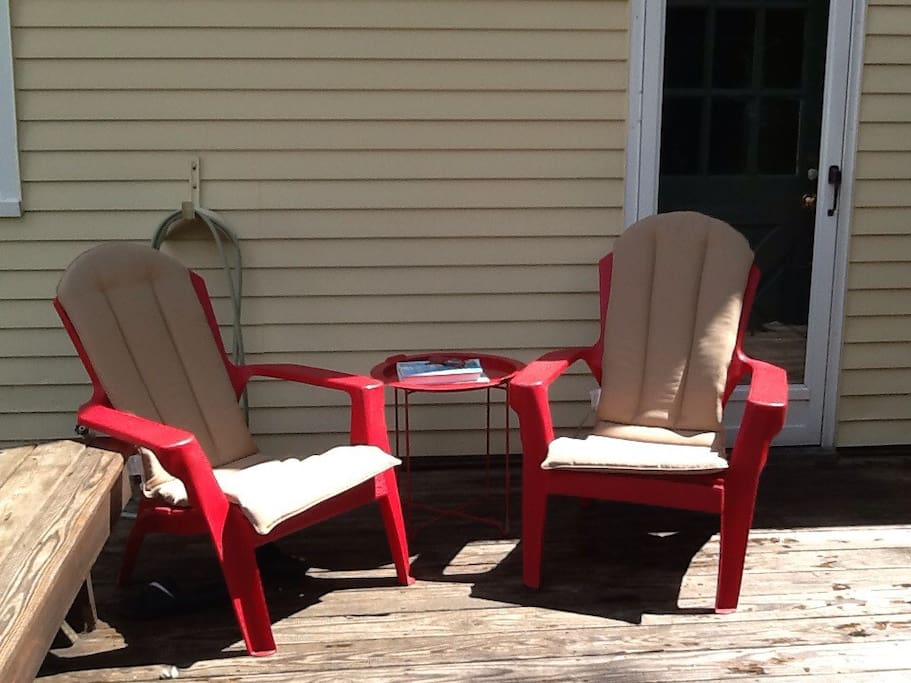 Comfortable chairs with new cushions just up the stairs and out the door to the deck.