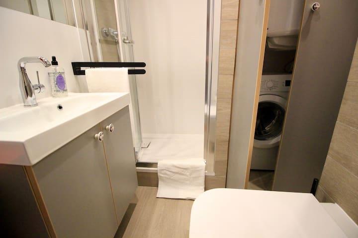 Bathroom with shower and washing machine.