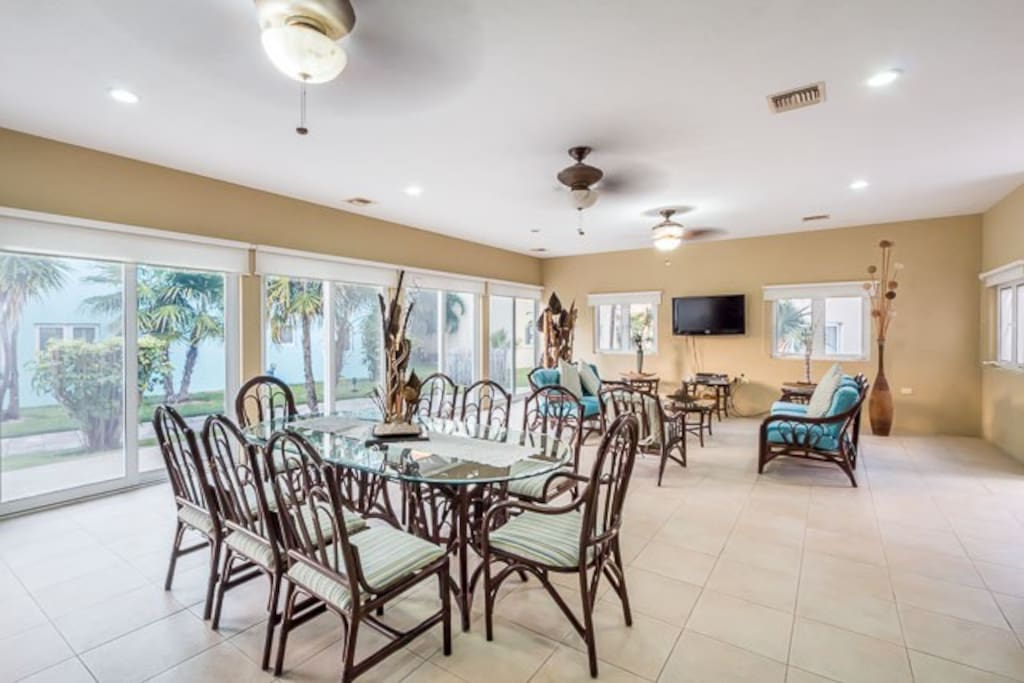 Large ground floor living area with elegant wicker furniture , a dining room with seating for 8, and flat screen TV with cable