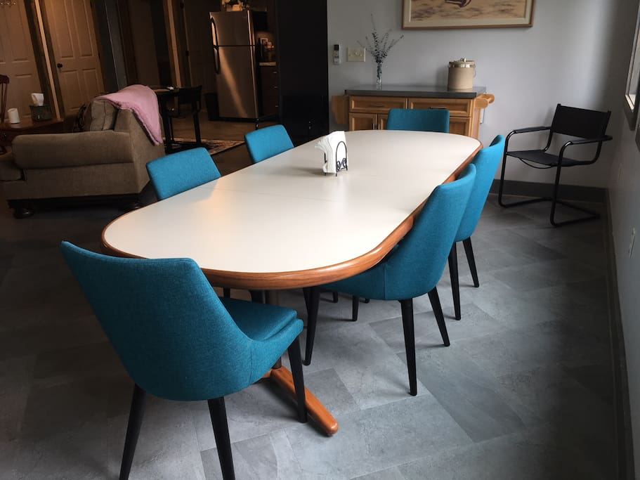 The dining area has a large table that can seat 8 people.