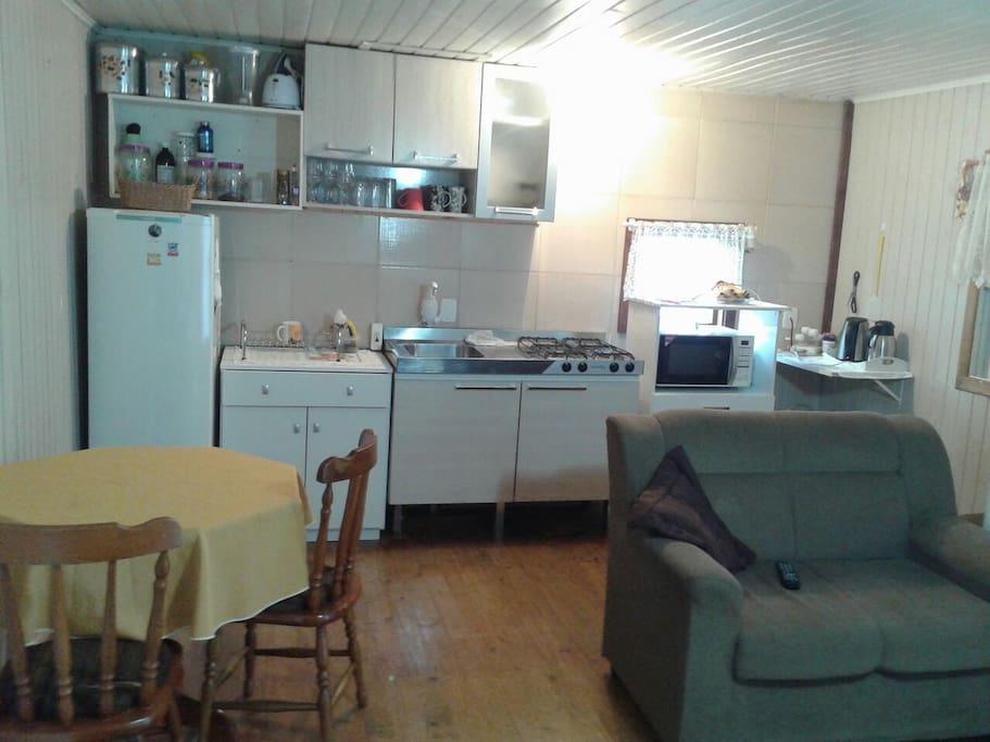 Cozinha com todos os utensílios indispensáveis, tais como: Fogão, pia, geladeira, jarra elétrica, microondas coberta de mesa etc.