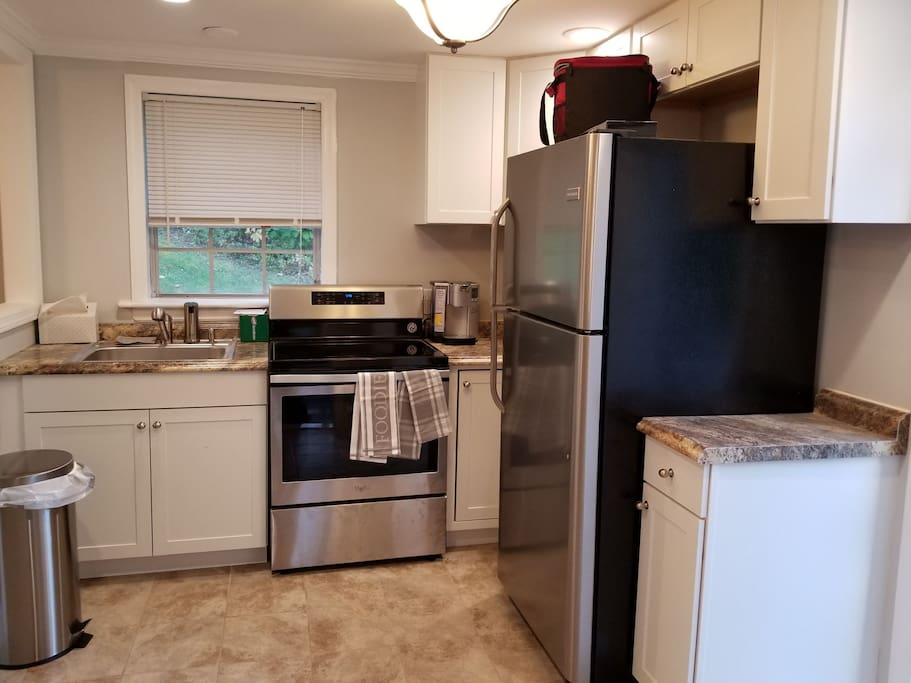 New kitchen with stainless steel appliances. Dishes, glasses, pans, silverware, toaster oven and coffee pot