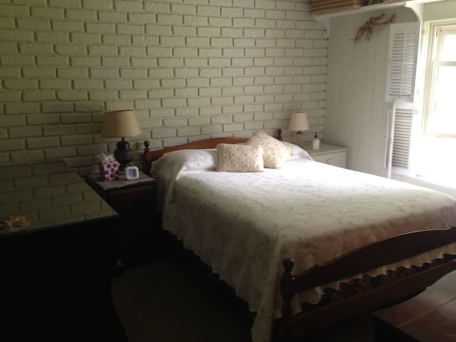 Bedroom with double bed. Walk-in closet facing foot of bed and huge early 20th century dresser on left
