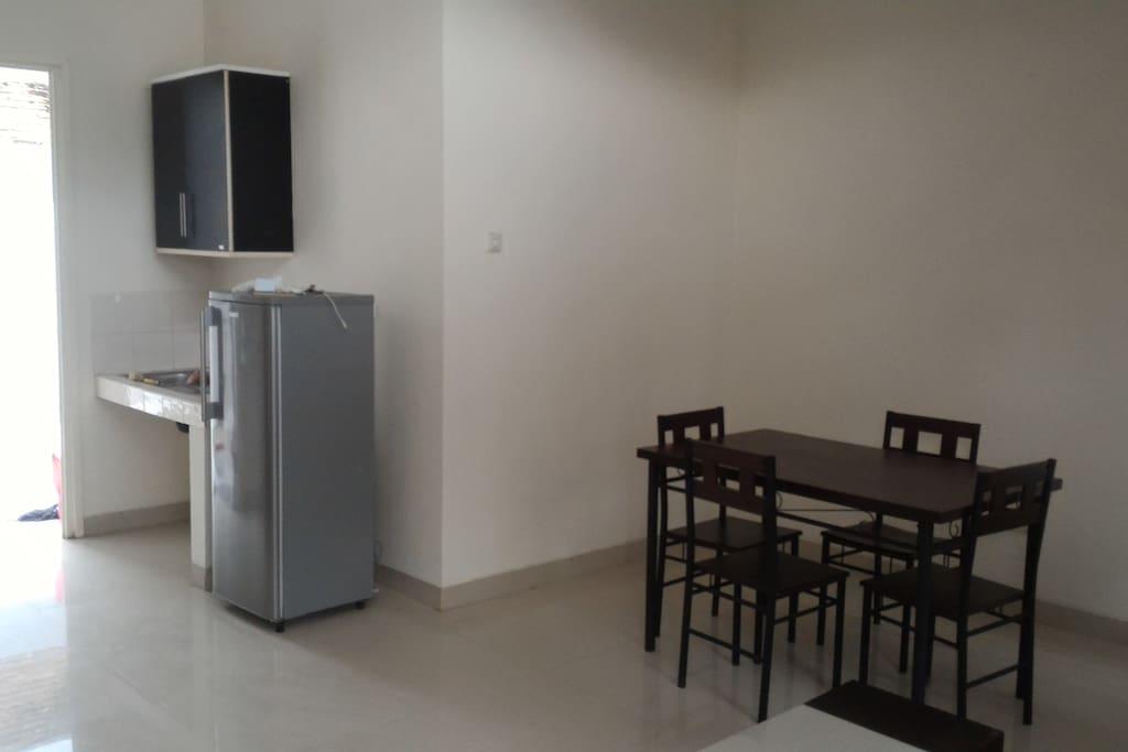 ruang makan dan sekaligus ruang tamu dengan kulkas yang siap diisi minuman dingin