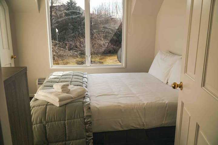 Upstairs bedroom with double bed, tallboy drawers and wardrobe