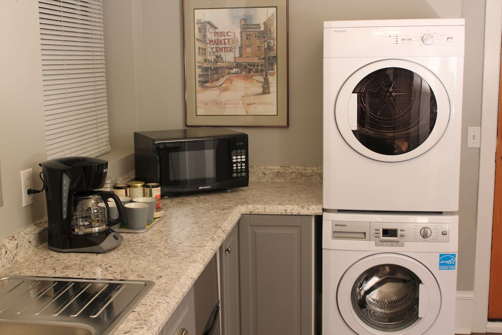 Kitchen appliances include oven with four-burner cook top, refrigerator, microwave, coffee maker, and European-made washer and dryer.