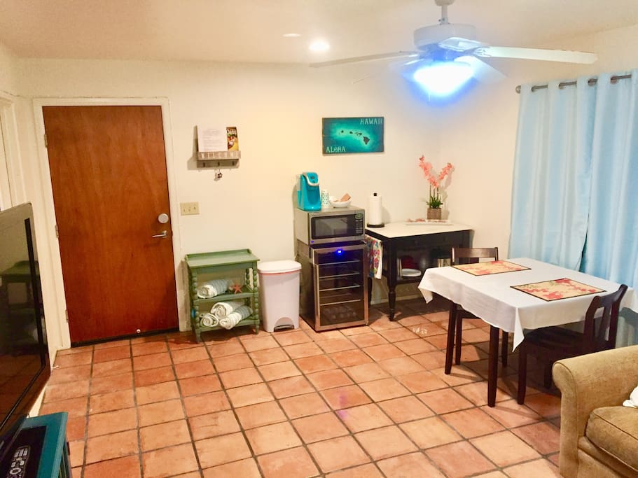 The great room with mini fridge, microwave, rolling kitchen island, and dining table