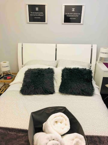 Modern, chic, big, bright room with a double size mattress and fur rug, side table with lamp, basket with 3 towels, throw blanket and decorative pillows.